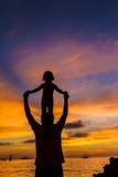 Père et enfant sur le fond de mer de coucher du soleil Photographie stock libre de droits
