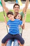 Père et enfants appréciant la conduite d'oscillation Images stock