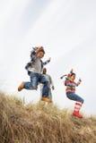 Père et enfants ayant l'amusement en dunes de sable Photo libre de droits