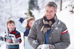 Père et enfants ayant le combat de boule de neige Photos stock