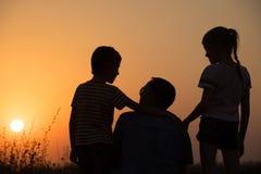 Père et enfants jouant en parc au temps de coucher du soleil Photographie stock libre de droits