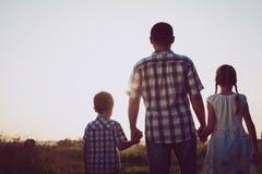 Père et enfants jouant en parc au temps de coucher du soleil Image stock