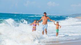 Père et enfants jouant sur la plage Images stock