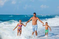 Père et enfants jouant sur la plage Photo stock