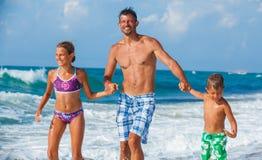 Père et enfants jouant sur la plage Photographie stock