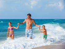 Père et enfants jouant sur la plage Photos libres de droits