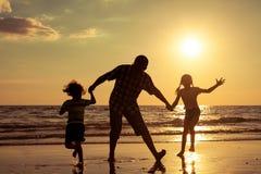 Père et enfants jouant sur la plage au temps de coucher du soleil Image stock