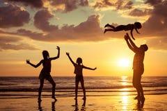 Père et enfants jouant sur la plage au temps de coucher du soleil Images libres de droits