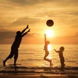Père et enfants jouant sur la plage au temps de coucher du soleil Images stock
