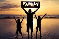 Père et enfants jouant sur la plage au temps de coucher du soleil Photographie stock