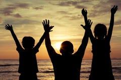 Père et enfants jouant sur la plage au temps de coucher du soleil Image libre de droits