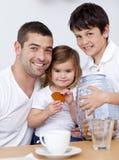 Père et enfants mangeant des biscuits avec du lait images libres de droits