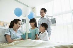 Père et enfants rendant visite à leur mère dans l'hôpital, donnant le présent et les ballons Image stock