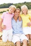 Père et enfants s'asseyant sur des balles de paille dans Harv Photos libres de droits