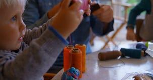 Père et enfants tenant des bobines de fil dans le salon à la maison 4k clips vidéos