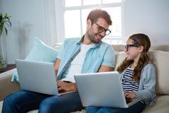 Père et fille à l'aide de l'ordinateur portable dans le salon Images libres de droits