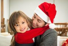 Père et fille étreignant dans Noël Photo stock