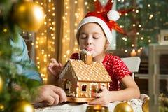 Père et fille adorable dans la maison de pain d'épice rouge de Noël de bâtiment de chapeau Image stock