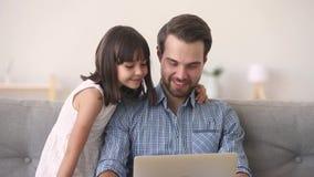 Père et fille ayant l'ordinateur en ligne de écoute d'utilisation de musique d'amusement clips vidéos