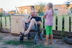 Père et fille dans la cour de la maison rurale Vie quotidienne Photographie stock libre de droits