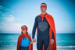 Père et fille dans le bord de mer de costume de super héros Photos stock
