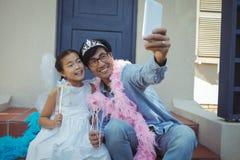 Père et fille dans le costume féerique prenant un selfie Image libre de droits
