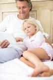 Père et fille de sourire à l'aide du comprimé numérique sur le lit Photographie stock libre de droits