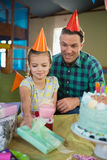 Père et fille de sourire dans le chapeau de partie regardant le boîte-cadeau Photo libre de droits