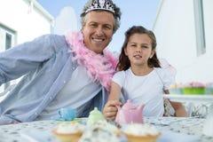 Père et fille de sourire dans le costume féerique ayant un thé Photographie stock libre de droits