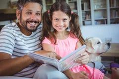 Père et fille de sourire regardant l'album photos dans le salon image libre de droits