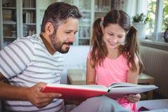 Père et fille de sourire regardant l'album photos dans le salon Photo stock