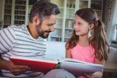 Père et fille de sourire regardant l'album photos dans le salon Photographie stock