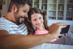 Père et fille de sourire regardant le téléphone portable dans le salon Photo stock