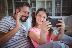 Père et fille de sourire regardant le téléphone portable dans le salon Photographie stock libre de droits