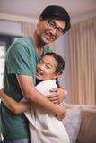 Père et fille de sourire s'étreignant dans le salon Photos libres de droits