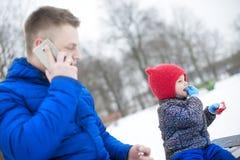 Père et fille en parc sur un banc Photo stock