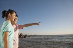 Père et fille indiquant et regardant la mer photographie stock