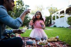Père et fille jouant avec des bulles de savon Photo stock