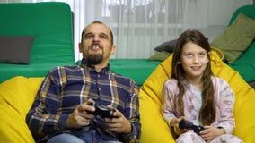 Père et fille jouant des gamepads ensemble à la maison clips vidéos