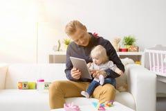 Père et fille jouant des jeux sur la tablette photographie stock libre de droits