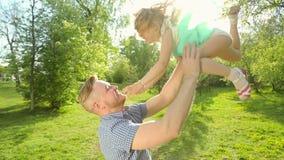 Père et fille jouant en été, il la jette dans l'air banque de vidéos