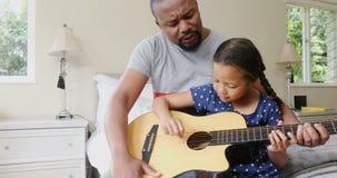 Père et fille jouant la guitare dans la chambre à coucher 4k clips vidéos