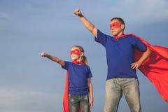 Père et fille jouant le super héros dehors au temps de jour Image libre de droits