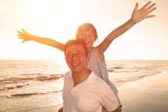 Père et fille jouant sur la plage Photo stock