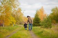 Père et fille marchant ensemble, jour d'automne Photographie stock