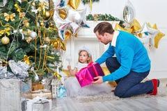 Père et fille mettant des cadeaux sous l'arbre de Noël photographie stock libre de droits