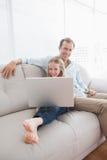 Père et fille occasionnels à l'aide de l'ordinateur portable sur le divan Photographie stock libre de droits