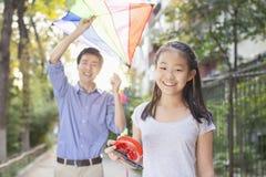 Père et fille pilotant un cerf-volant Photographie stock libre de droits
