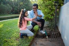 Père et fille plantant un arbre dans le jardin à l'arrière-cour Images stock