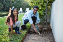 Père et fille plantant un arbre dans le jardin à l'arrière-cour Photographie stock libre de droits